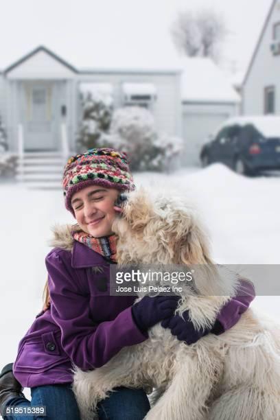 Caucasian girl hugging dog in winter