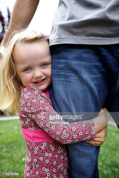 Caucasian girl hugging father's leg