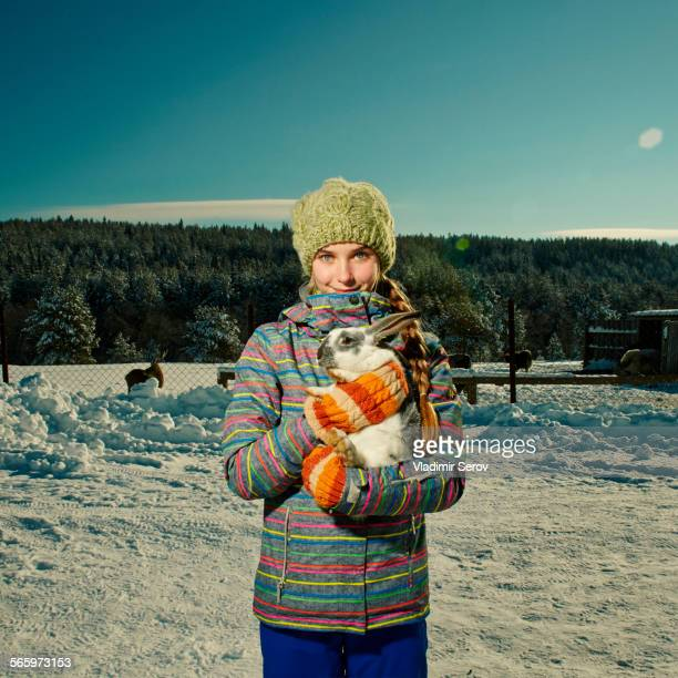 Caucasian girl hugging rabbit in snowy field