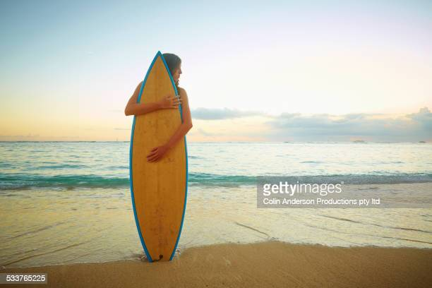 Caucasian girl hugging surfboard on beach