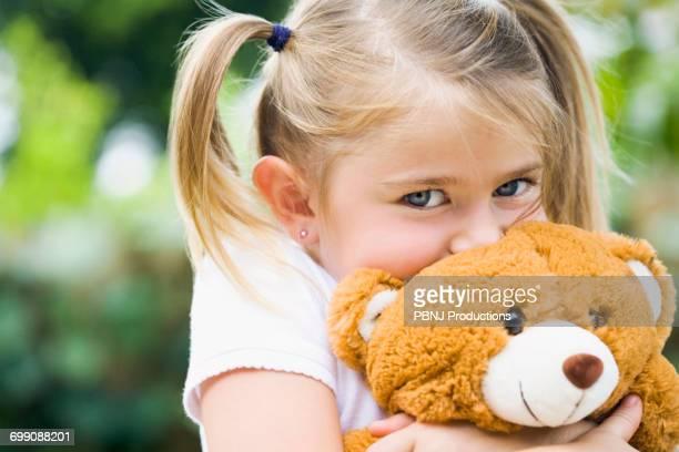Caucasian girl hugging teddy bear