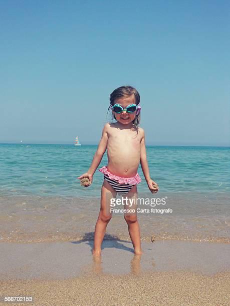 Caucasian girl in bathing suit standing on beach