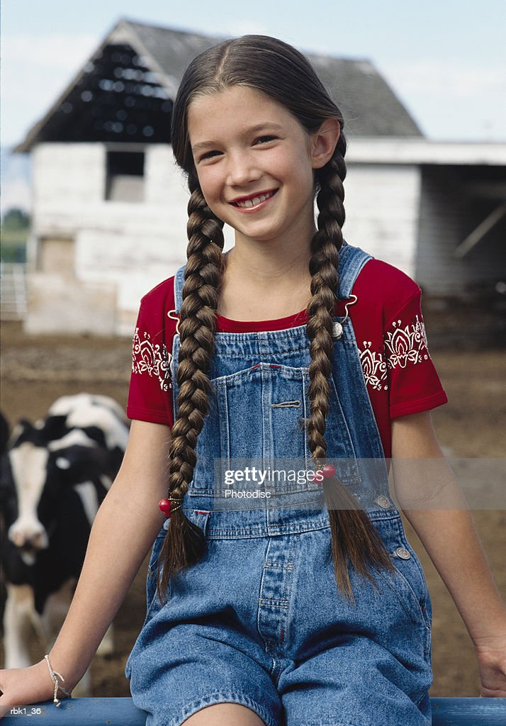 A caucasian girl in braided hair sits on a fence at a farm : Stockfoto