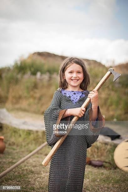 Caucasian girl in chain mail carrying hatchet in backyard