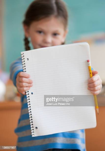Caucasian girl in classroom holding notebook and pencil