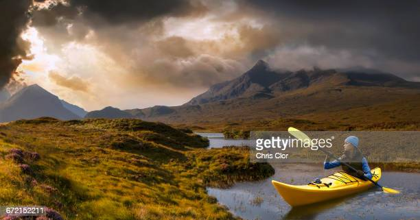 caucasian girl in kayak on mountain river - kajak stock-fotos und bilder