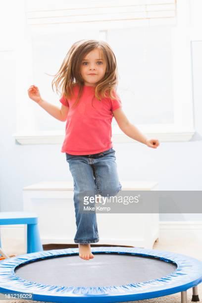 Caucasian girl jumping on trampoline