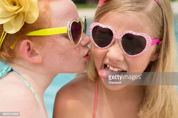 Caucasian girl kissing cheek of friend near swimming pool