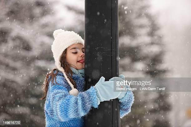 Caucasian girl kissing frozen pole in snow
