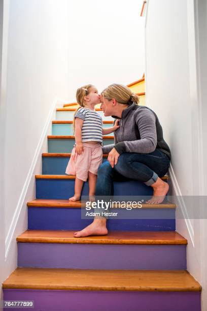 Caucasian girl kissing mother on forehead on multicolor staircase