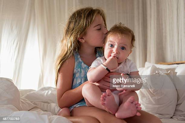 Caucasian girl kissing sibling on sofa