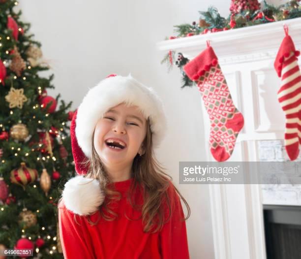 Caucasian girl laughing in Santa hat