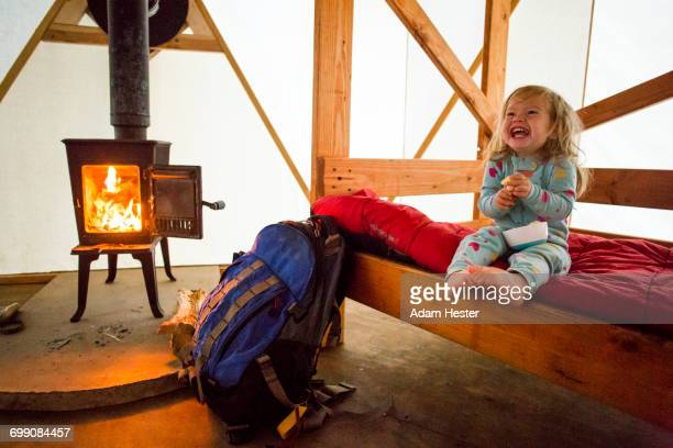 Caucasian girl laughing on bed in yurt