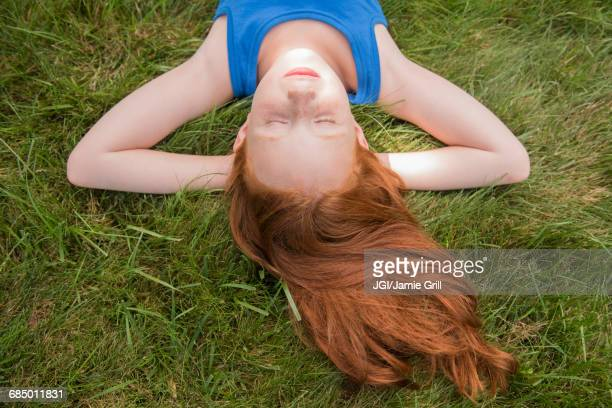 Caucasian girl laying in grass with hands behind head