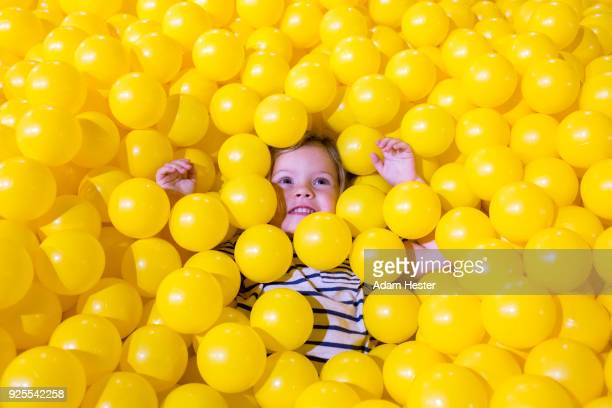 caucasian girl laying in pile of yellow balls - spielball stock-fotos und bilder