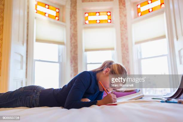 Caucasian girl laying on bed writing in notebook