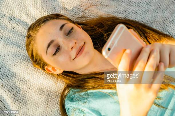 caucasian girl laying on blanket texting on cell phone - tienermeisjes stockfoto's en -beelden