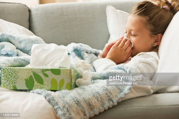 Caucasian girl laying on couch blowing her nose