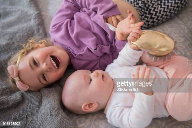 Caucasian girl laying on floor with baby sister