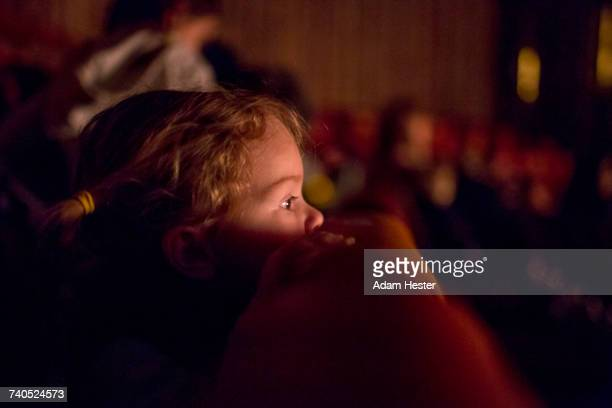 Caucasian girl leaning on chair watching movie in theater