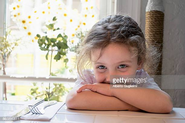 Caucasian girl leaning on kitchen table