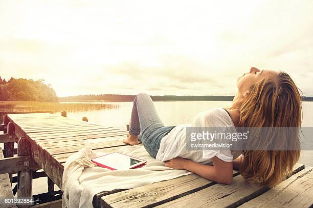 Caucasian girl lies on jetty above lake at sunset