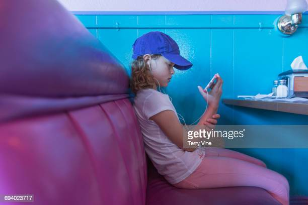 Caucasian girl listening to cell phone in restaurant booth