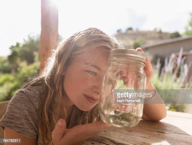 Caucasian girl looking at jar
