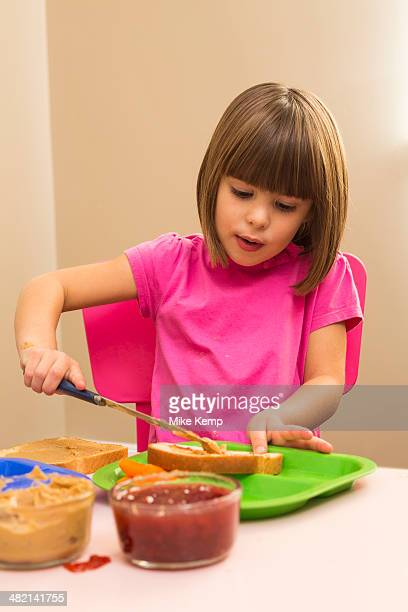 Caucasian girl making sandwich in kitchen