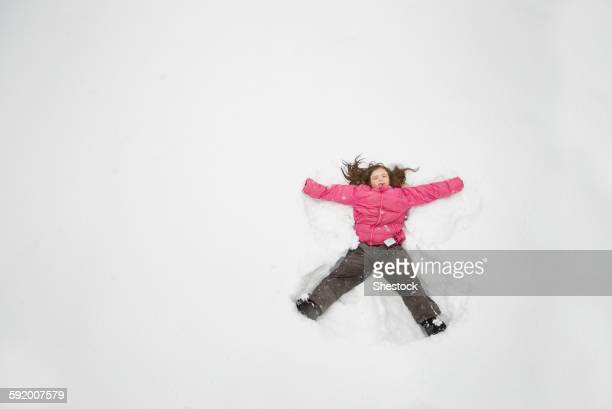 Caucasian girl making snow angel