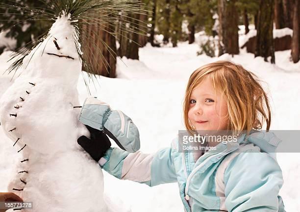 Caucasian girl making strange snowman