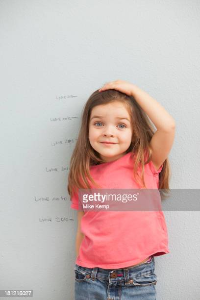 caucasian girl measuring her height on wall - measuring fotografías e imágenes de stock