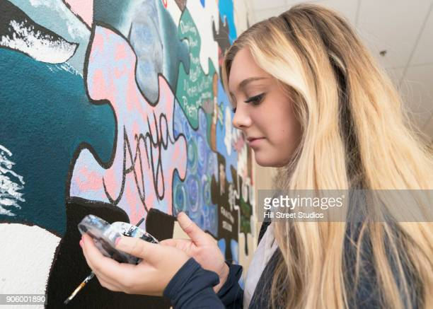 caucasian girl mixing paint for wall mural in school - teenagers only stock pictures, royalty-free photos & images