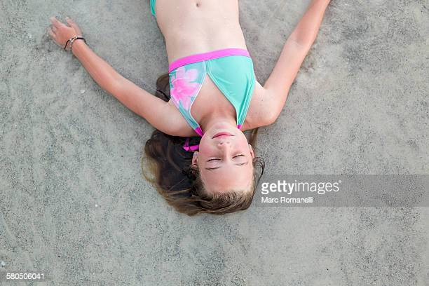 Caucasian girl napping on beach