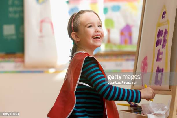 caucasian girl painting in art class - staffelei stock-fotos und bilder