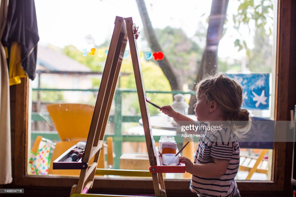 Caucasian girl painting on easel near window : Stock Photo