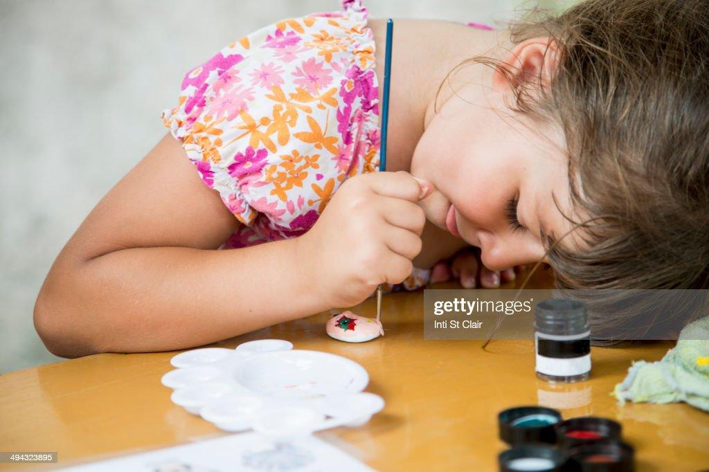 Caucasian girl painting rock on desk : Stock Photo