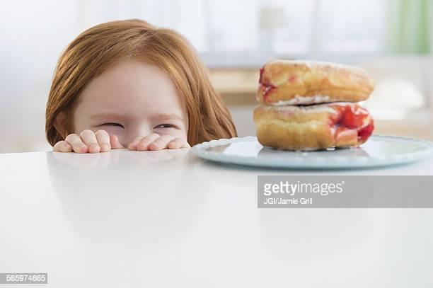 Caucasian girl peeking at donuts on table