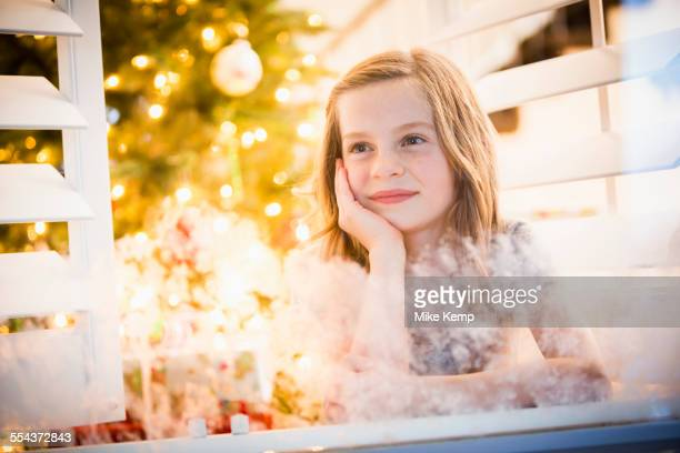 Caucasian girl peering out window at Christmas