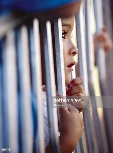 a caucasian girl peers through bars with patience - child behind bars stock pictures, royalty-free photos & images