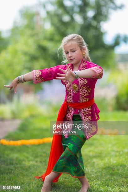 Caucasian girl performing Balinese dance in backyard