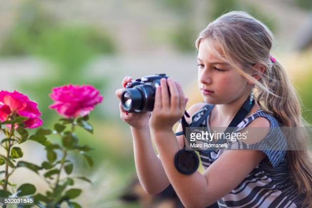 Caucasian girl photographing flowers outdoors