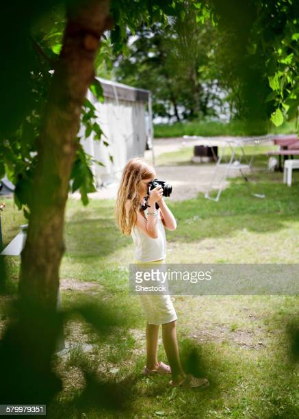 Caucasian girl photographing in backyard