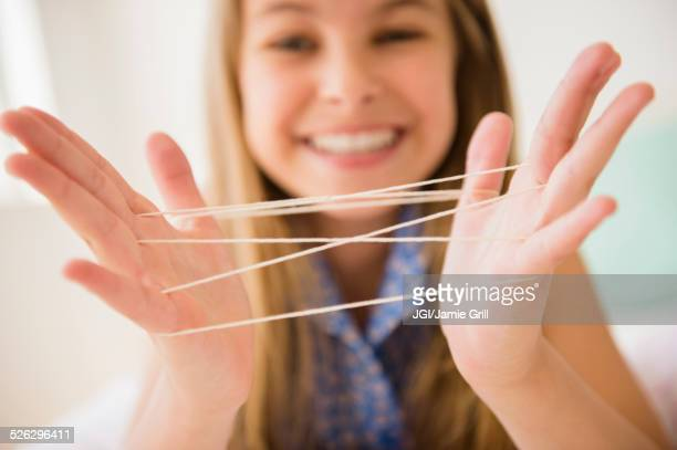 Caucasian girl playing cats cradle game