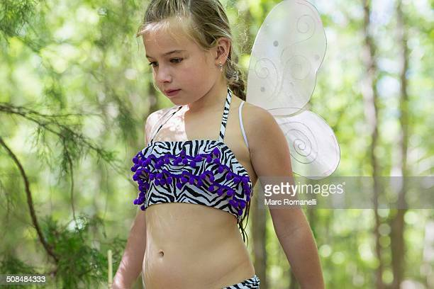 Caucasian girl playing dress up in forest