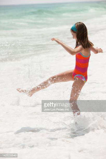 Caucasian girl playing in ocean