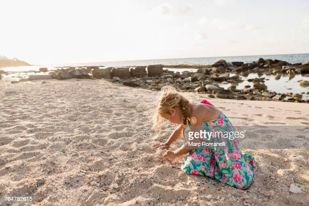 Caucasian girl playing in sand at beach