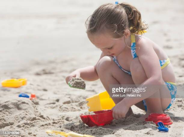 Caucasian girl playing in the sand