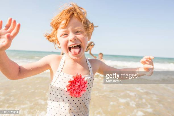 Caucasian girl playing in waves on beach