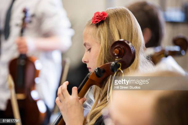 Caucasian girl playing instrument in music class